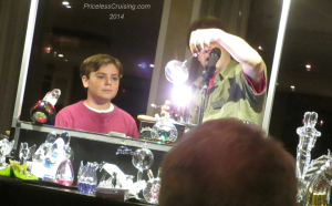 Max, the token child onboard, participating in the glass blowing demonstration